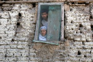 People look out from a window as they watch a protest against the recent killings in Kashmir, on the outskirts of Srinagar