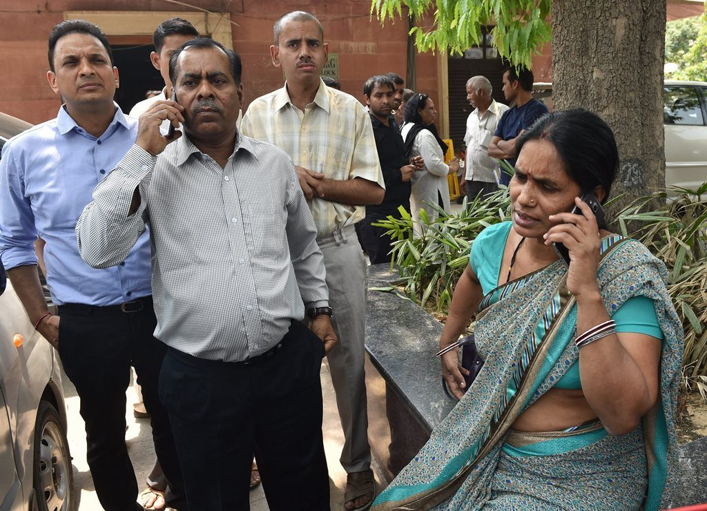 New Delhi: Nirbhayas parents talk on phone at the Supreme Court in New Delhi on Friday. The apex court has confirmed death sentence for the four convicts of Nirbhaya gang rape case who raped and tortured the 23-year-old medical student on a moving bus in Delhi on her way home on Dec 16, 2012. PTI Photo by Manvender Vashist