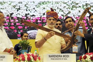 """The Prime Minister, Shri Narendra Modi being presented a """"Plough"""" as symbol of farming at the launching ceremony of DD Kisan Channel, in New Delhi on May 26, 2015.  The Union Minister for Agriculture, Shri Radha Mohan Singh is also seen."""
