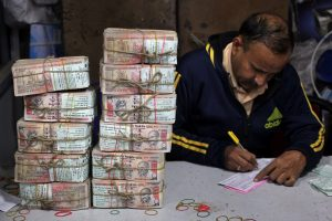 A bank employee fills a form after counting stacks of old 1000 Indian rupee banknotes inside a bank in Jammu, November 25, 2016. REUTERS/Mukesh Gupta - RTST9NC