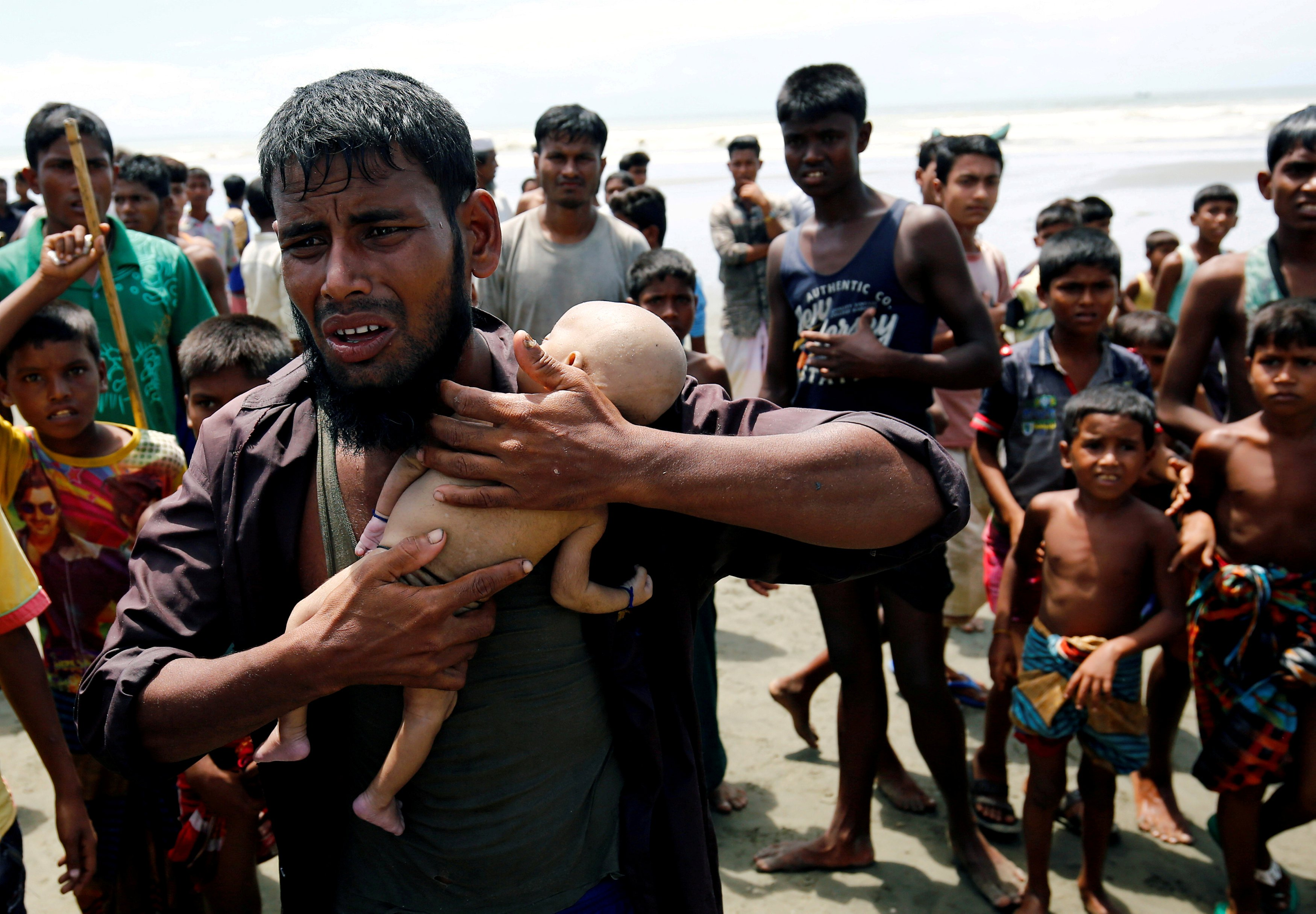 Ahmed, a Rohingya refugee man cries as he holds his 40-day-old son, who died as a boat capsized in the shore of Shah Porir Dwip while crossing Bangladesh-Myanmar border, in Teknaf, Bangladesh. Reuters