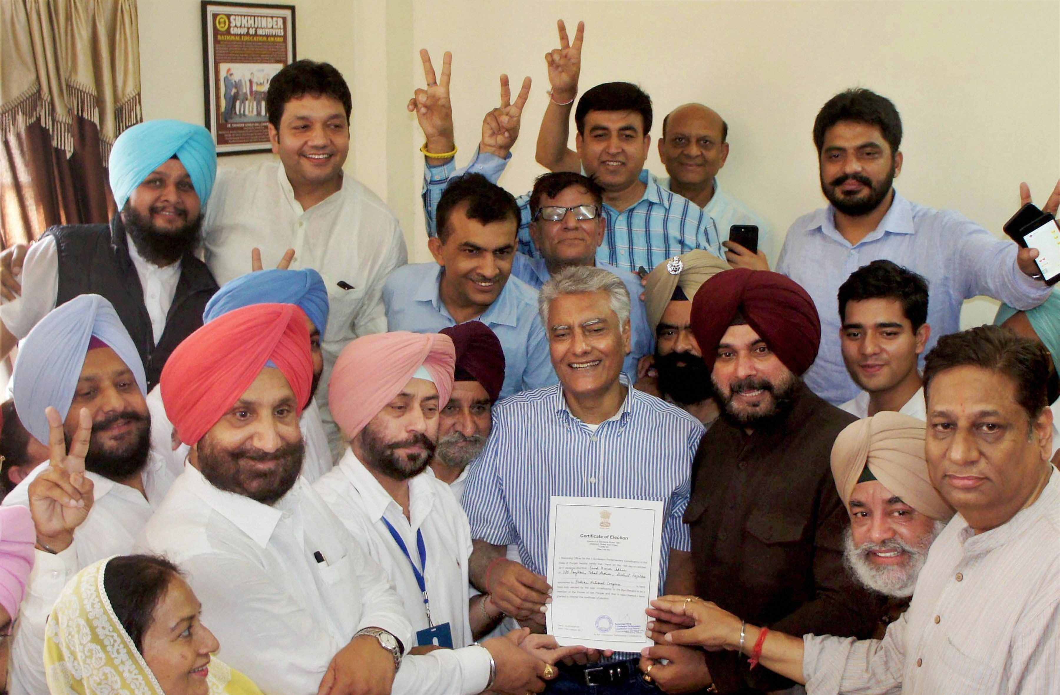 Gurdaspur: Punjab Congress president Sunil Jakhar with State Cabinet minister Navjot Singh Sidhu and other party leaders showing his victory certificate as he celebrates after winning the Gurdaspur parliamentary bypoll, in Gurdaspur on Sunday. PTI Photo (PTI10_15_2017_000046B)
