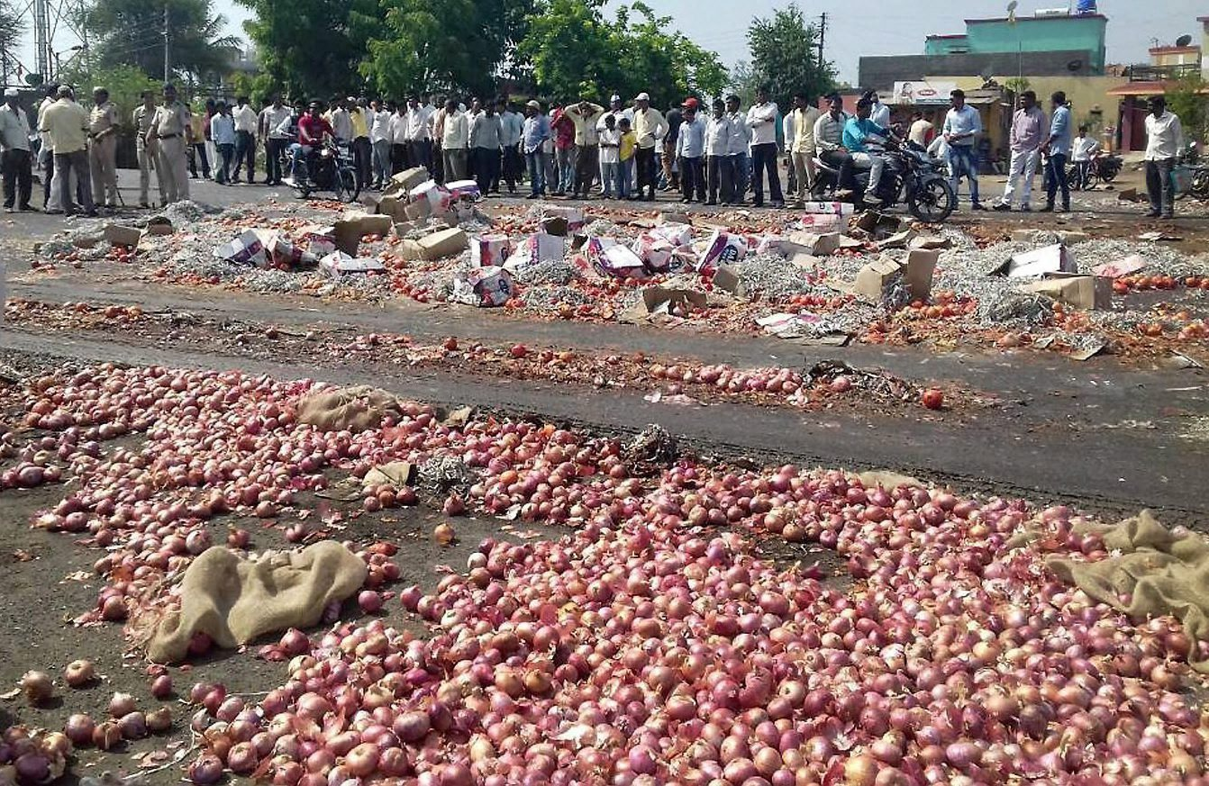Nashik: Farmers throwing onions and other vegetables on the road during their state-wide strike over various demands in Nasik, Maharashtra on Thursady. PTI Photo  (PTI6_1_2017_000201B)