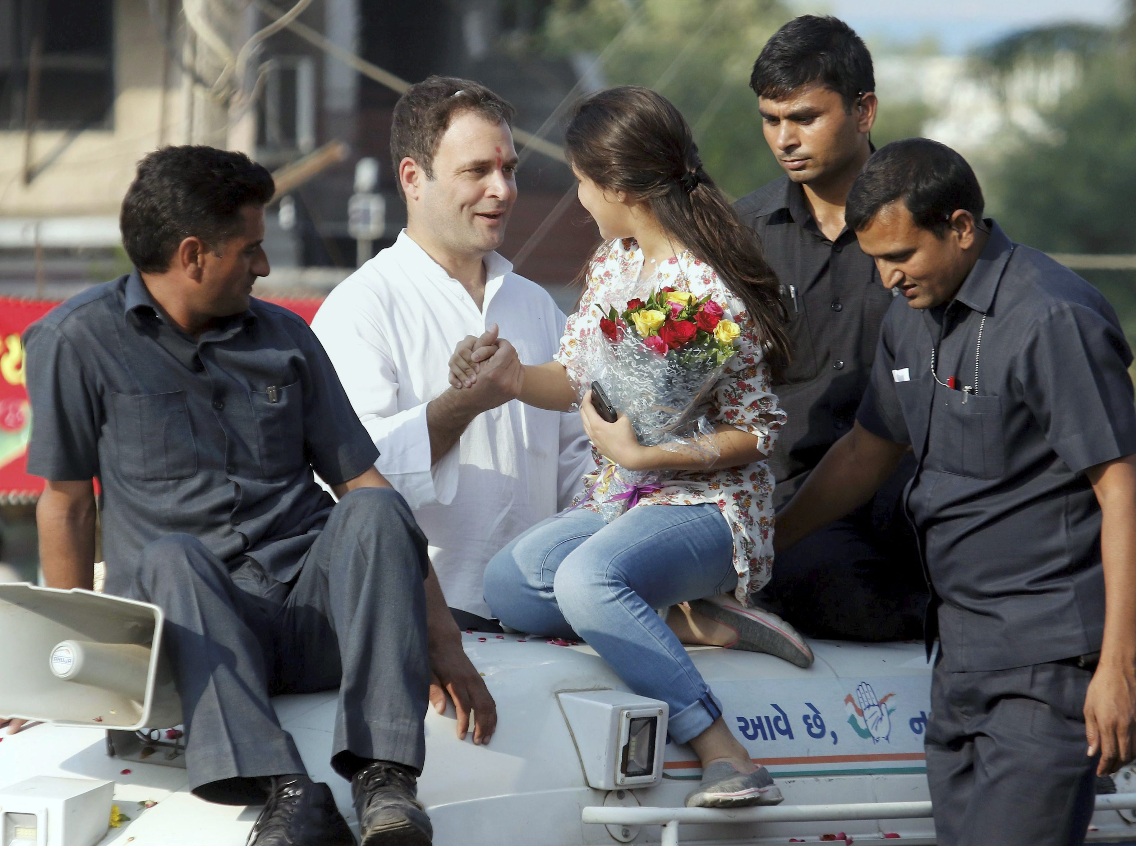 Bharuch: Congress vice-president Rahul Gandhi being greeted by a young supporter during his road show in Bharuch on Wednesday. PTI Photo (PTI11_1_2017_000100B)