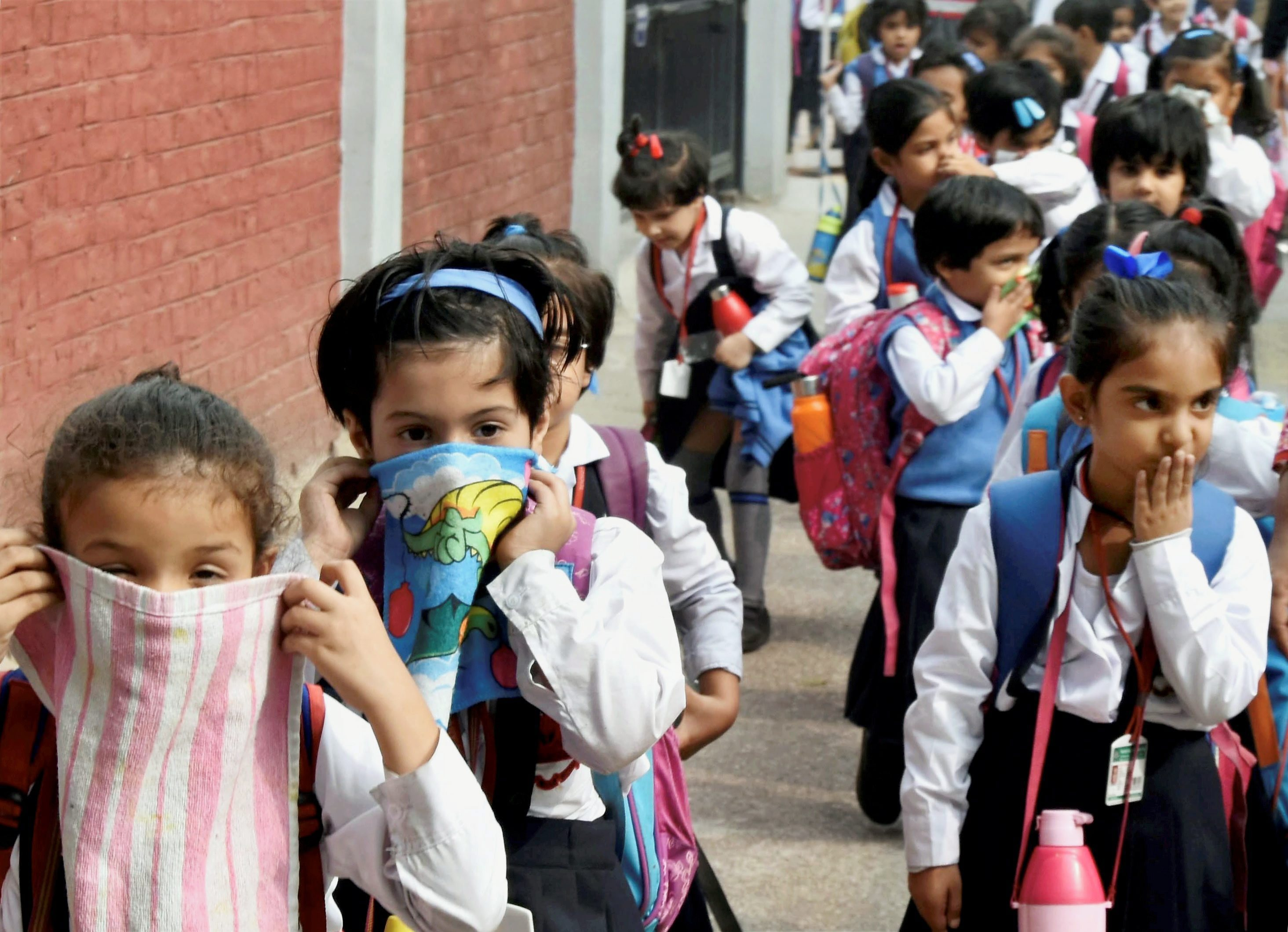 New Delhi: School children cover their noses as air pollution reached hazardous levels in New Delhi on Tuesday. PTI Photo (PTI11_7_2017_000089A) *** Local Caption ***