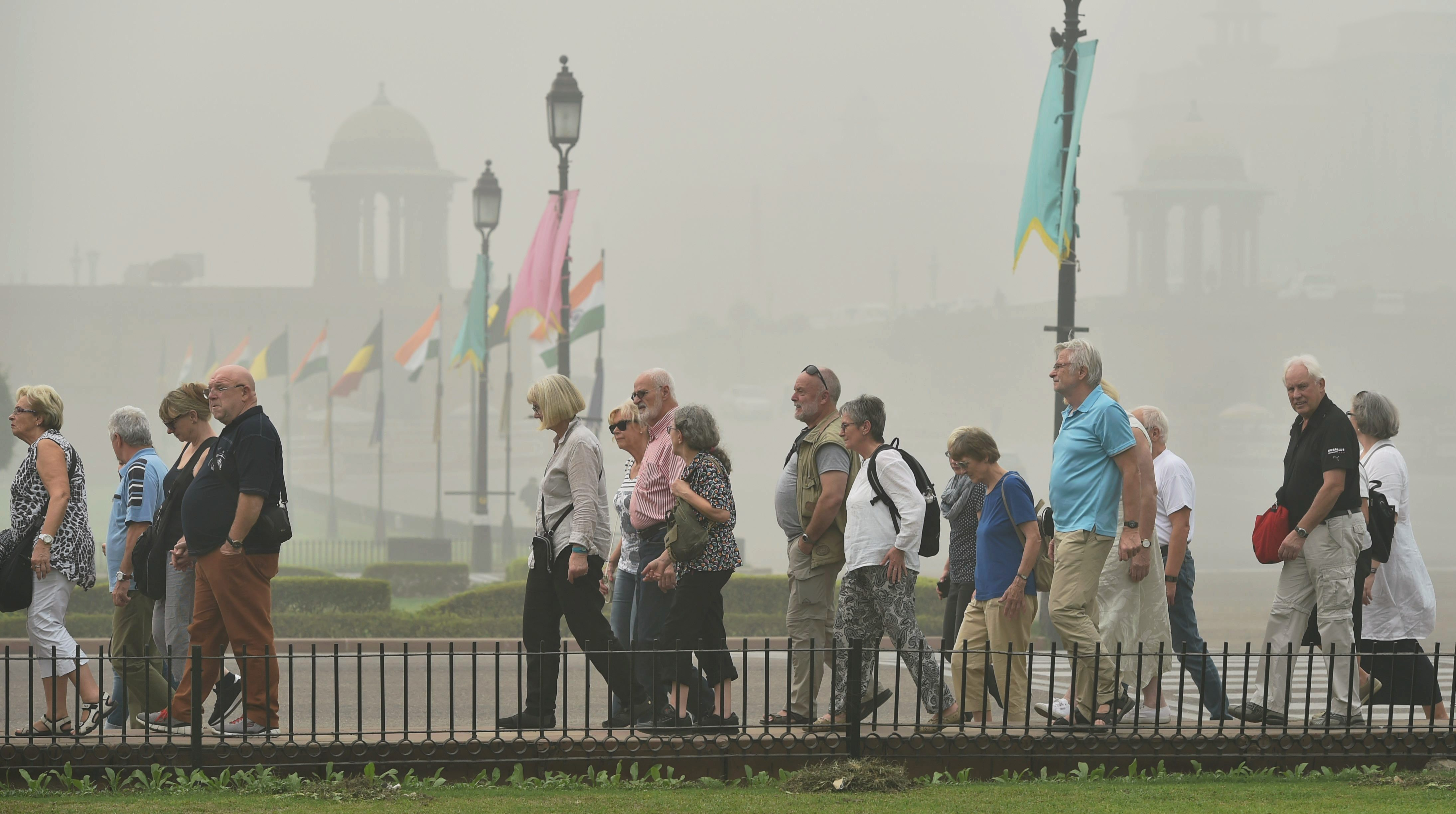 New Delhi: A group of foreign tourists at Vijay Chowk during heavy smog and air pollution in New Delhi on Wednesday. The smog and air pollution continue to be above the severe levels in Delhi NCR. PTI Photo by Vijay Verma(PTI11_8_2017_000092B)