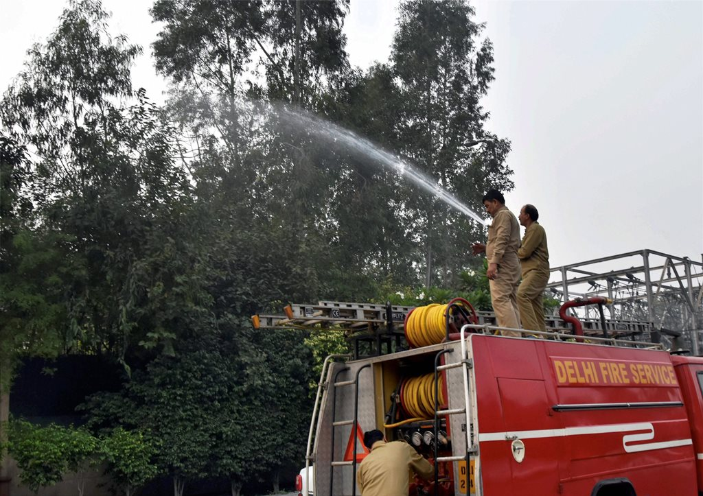 New Delhi: Fire services personnel sprinkling water on the trees to settle the dust as part of the pollution-control measures in New Delhi on Thursday. PTI Photo (PTI11 9 2017 000167A)