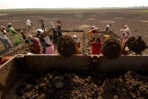 Labourers load a truck as they try to revive a dried lake under the National Rural Employment Guarantee Act (NREGA) at Ibrahimpatnam, on the outskirts of Hyderabad, June 17, 2009. The government has started a pilot project to quantify climate benefits from the NREGA, the anti-poverty scheme that could become one of the country's main weapons to fight criticism it is not doing enough to tackle global warming. The flagship anti-poverty plan, started three years ago, provides 100 days of employment every year to tens of millions of rural poor, a move that partly helped the Congress party-led coalition return to power in a general election. REUTERS/Krishnendu Halder (INDIA ENVIRONMENT BUSINESS EMPLOYMENT) - RTR24QZU