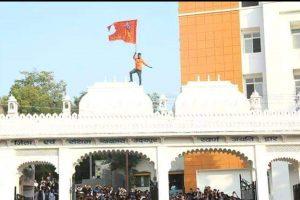उदयपुर की अदालत की छत पर भगवा झंडा फहराता युवक. (फोटो साभार: दैनिक भास्कर)