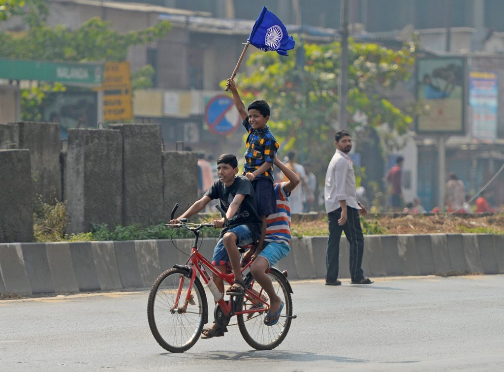 Mumbai: Boys carry a flag while riding a bicycle across a deserted road after Dalits called for Maharashtra Bandh as a protest over Bhima Koregaon violence, in Mumbai on Wednesday. PTI Photo by Shashank Parade(PTI1_3_2018_000101B)