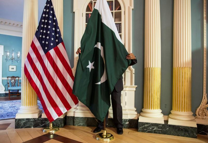 A State Department contractor adjust a Pakistan national flag before a meeting between U.S. Secretary of State John Kerry and Pakistan's Interior Minister Chaudhry Nisar Ali Khan on the sidelines of the White House Summit on Countering Violent Extremism at the State Department in Washington February 19, 2015. REUTERS/Joshua Roberts
