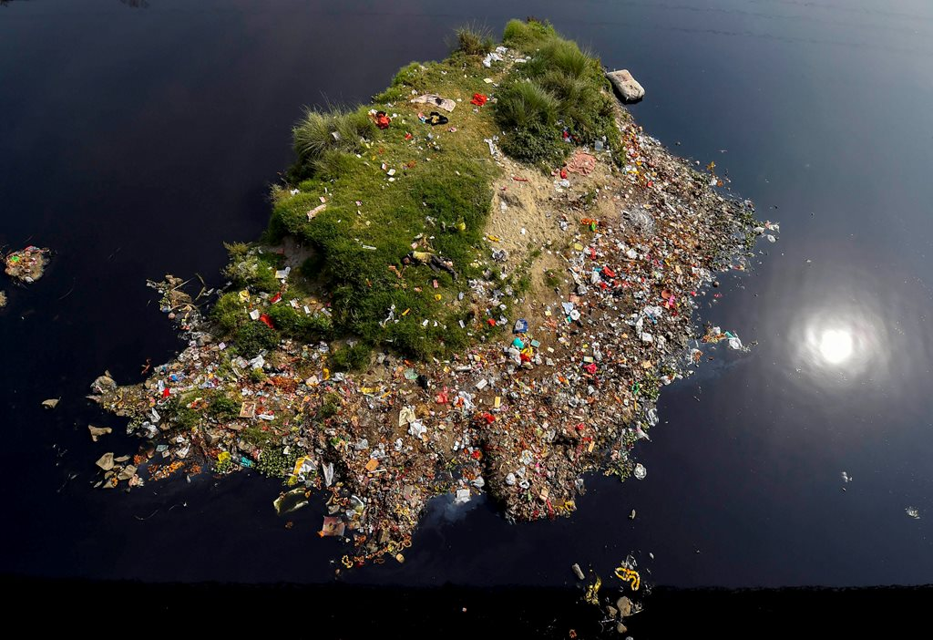 New Delhi: A view from the ITO bridge shows a small island covered with garbage, surrounded by the polluted waters of river Yamuna, in New Delhi, on Monday. According to the UN, the theme for World Water Day 2018, observed on March 22, is 'Nature for Water' – exploring nature-based solutions to the water challenges we face in the 21st century. PTI Photo by Ravi Choudhary(PTI3_21_2018_000119B)