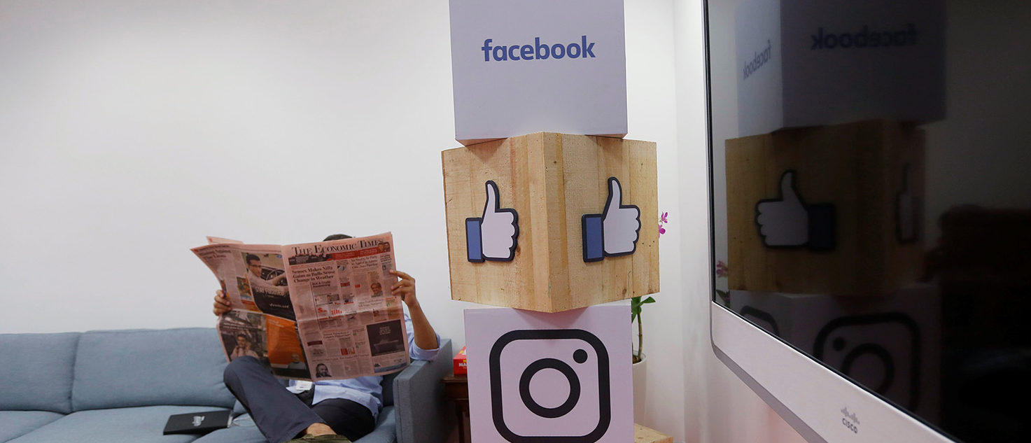A man reads a newspaper at the reception area of Facebook's new office in Mumbai, India May 27, 2016. REUTERS/Shailesh Andrade - S1BETGLTBMAB