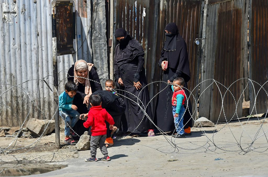 Srinagar: Women and children try to cross barbed wire placed to block a road during restrictions, in Srinagar on Thursday. Authorities have imposed restrictions in many parts of Srinagar and Kulgam district to maintain law and order. PTI Photo by S. Irfan (PTI4_12_2018_000164B)