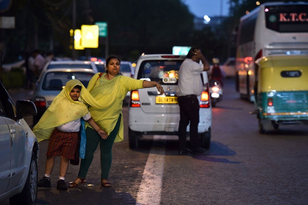 New Delhi: A lady and her child wait to hail a vehicle in New Delhi on Friday. PTI Photo by Arun Sharma (PTI4_6_2018_000158B)