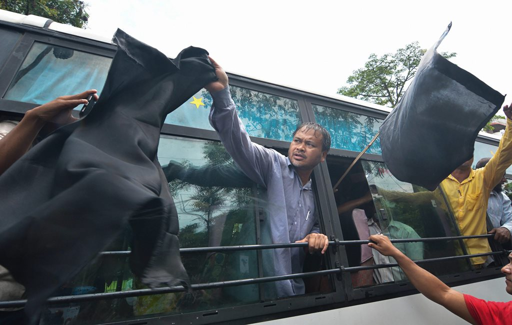 Guwahati: Krishak Mukti Sangram Samiti (KMSS) Advisior Akhil Gogoi waves black flags as he is detained along with supporters in bus, during a protest before the arrival of BJP President Amit Shah at Panjabari in Guwahati on Sunday. PTI Photo (PTI5_20_2018_000056B)