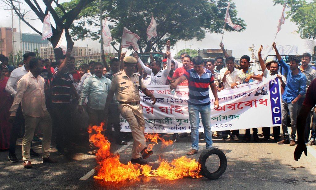 Guwahati: A policecman tries to extinguist a burning tyre as Asom Jatiyatabadi Yuba-Chatra Parishad activists participate in a National Highway Road block program to protest against Citizenship Amendment Bill Act 2016, in Guwahati on Saturday. PTI Photo (PTI5_12_2018_000095B)