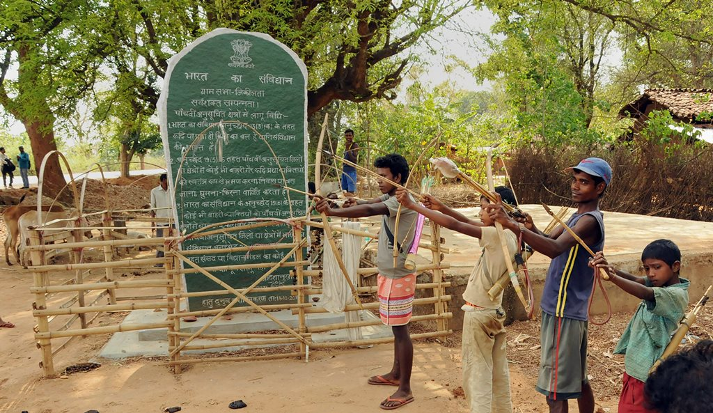 """Khunti: Tribals hold bows and arrows near a Patthalgarhi spot at Maoist-affected village Siladon under Khunti district of Jharkhand on Tuesday. The Patthalgarhi movement says that the """"gram sabha"""" has more weight than either the Lok Sabha or the Vidhan Sabha in scheduled areas. PTI Photo (PTI5_1_2018_000146B)"""