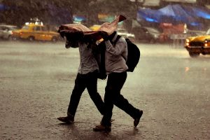Kolkata: Two men use a plastic sheet to protect themselves, as it rains in Kolkata on Sunday. (PTI Photo / Ashok Bhaumik) (PTI5_13_2018_000096B)