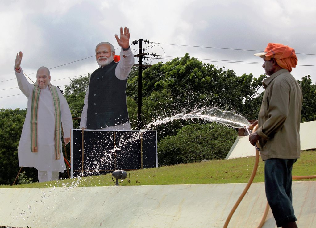 Bhubaneswar: A worker sprinkles water with the cutouts of Prime Minister Narendra Modi and BJP President Amit Shah in the backdrop, ahead of BJP's public meeting, in Bhubaneswar, on Friday.