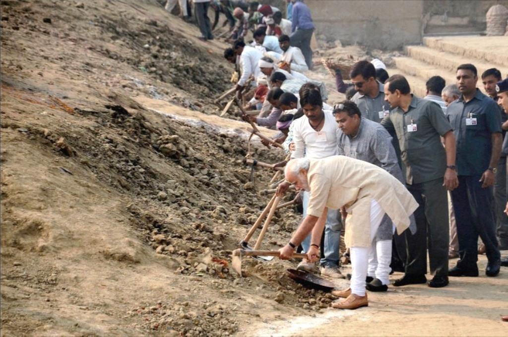 Varanasi: Prime Minister Narendra Modi wields a spade as he participates in the 'Swachh Bharat Campaign' at Assi Ghat in Varanasi on Saturday. PTI Photo(PTI11_8_2014_000024B)