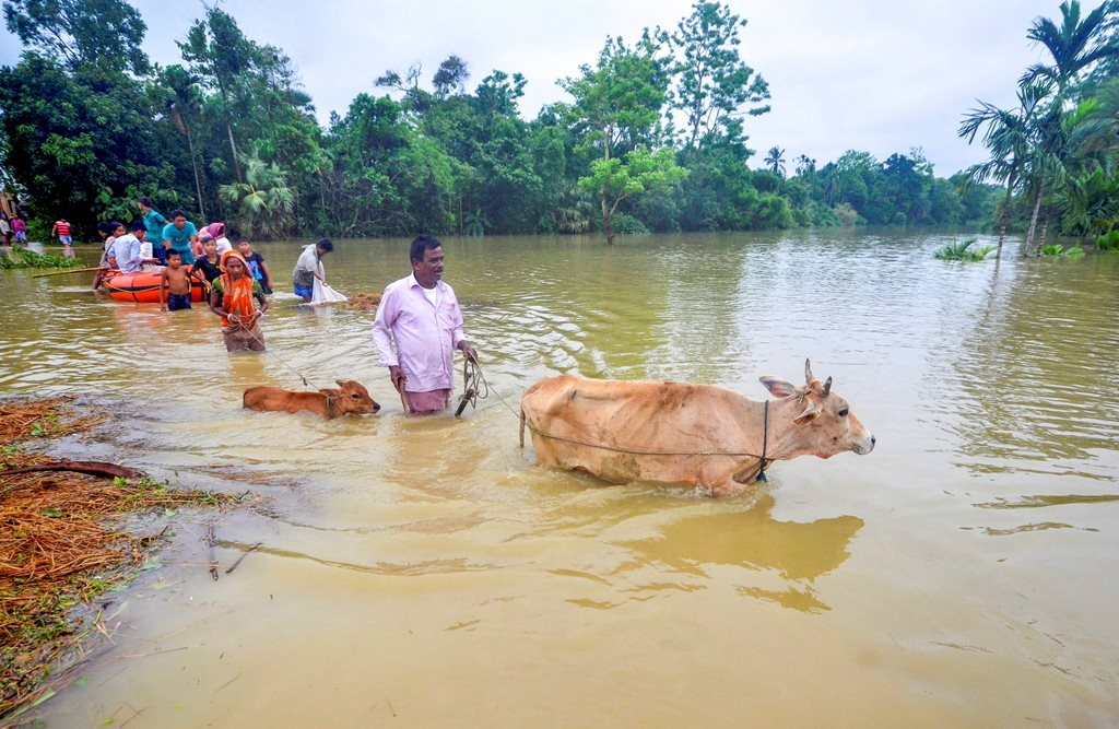 Agartala: Villagers shift from the flood affected Mog Para village after heavy downpour in Sabroom, about 137 kms from Agartala on Wednesday, June 13, 2018. (PTI Photo) (PTI6_13_2018_000051B)
