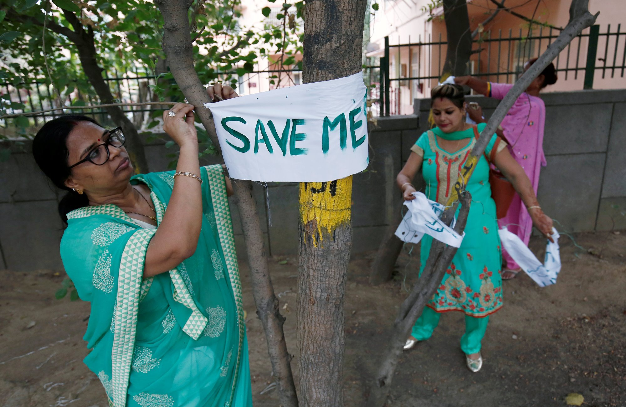 """A women tie banners on trees during """"Save The Tree Campaign"""" in New Delhi, India, June 26, 2018. REUTERS/Adnan Abidi"""