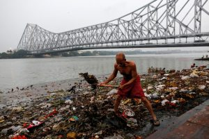 A man cleans garbage along the banks of the river Ganges in Kolkata, India, April 9, 2017. REUTERS/Danish Siddiqui
