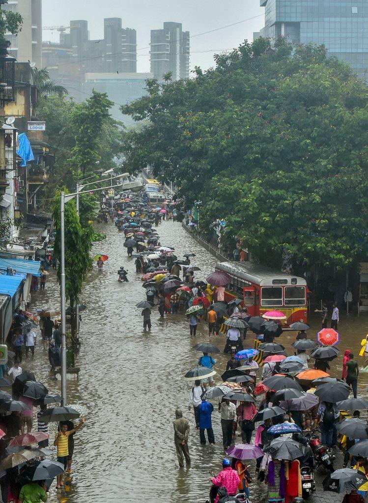 Mumbai: People take cover under umbrellas as they wade through a waterlogged street during rains, in Mumbai on Tuesday, July 10, 2018. (PTI Photo/Mitesh Bhuvad) (PTI7_10_2018_000129B)