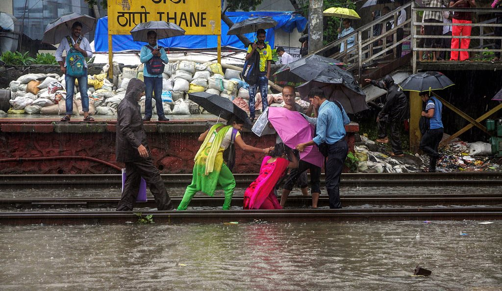 Thane: A woman is helped by other commuters after she fell on the tracks at Thane Railway Station during heavy rains, in Thane on Monday, July 9, 2018. (PTI Photo) (PTI7_9_2018_000049B)