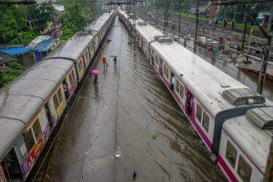 Thane: Suburban trains chug on water-logged tracks during heavy rainfall, in Mumbai on Monday, July 09, 2018. (PTI Photo) (PTI7_9_2018_000178B)