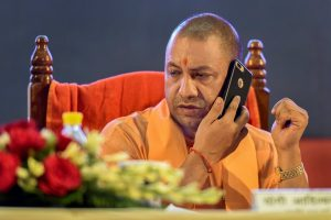 Lucknow: Uttar Pradesh Chief Minister Yogi Adityanath talks on a phone during an event, in Lucknow on Monday, Aug 6, 2018. (PTI Photo) (PTI8_6_2018_000127B)