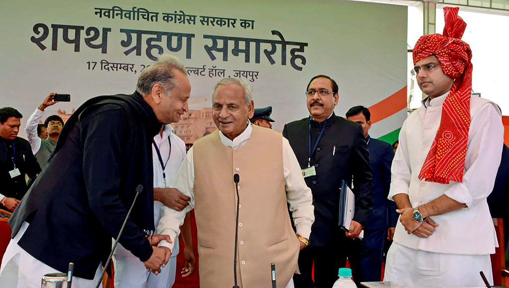 Jaipur: Rajasthan Governor Kalyan Singh shakes hands with newly sworn-in Chief Minister Ashok Gehlot as Deputy Chief Minister Sachin Pilot looks on, during the swearing-in-ceremony of Gehlot's government, in Jaipur, Monday, Dec. 17, 2018. (PTI Photo) (PTI12_17_2018_000128B)