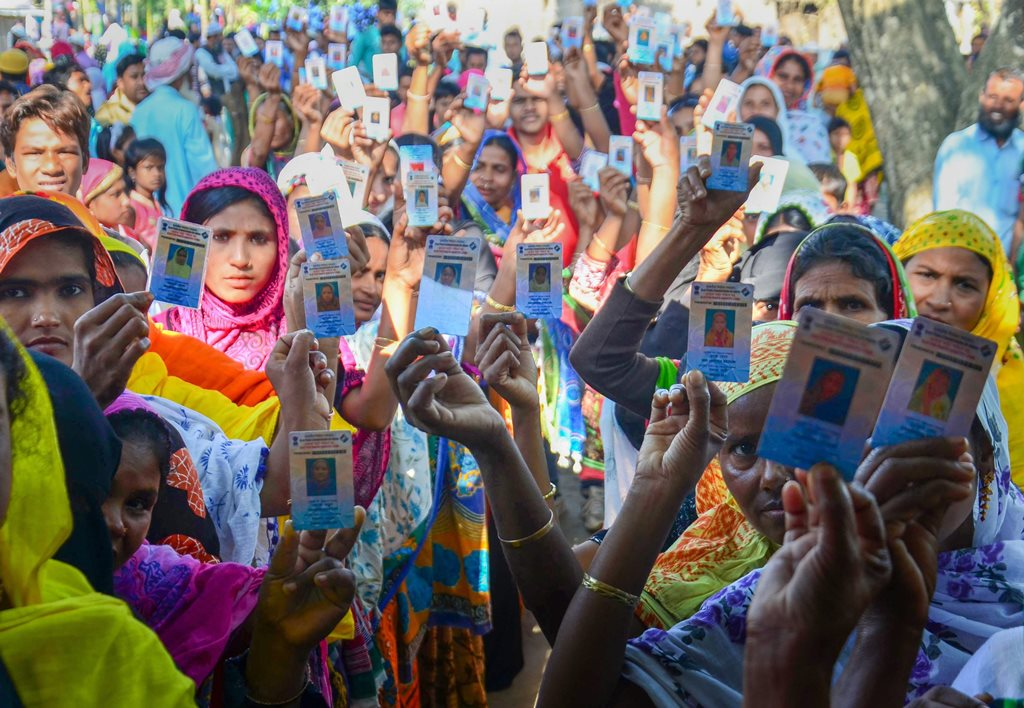 Kamrup: Voters show their ID cards while standing in a queue at a polling station during the 1st phase of the panchayat elections at Hatipara village, in Kamrup district, Assam, Wednesday, Dec. 05, 2018. (PTI Photo)(PTI12_5_2018_000042B)