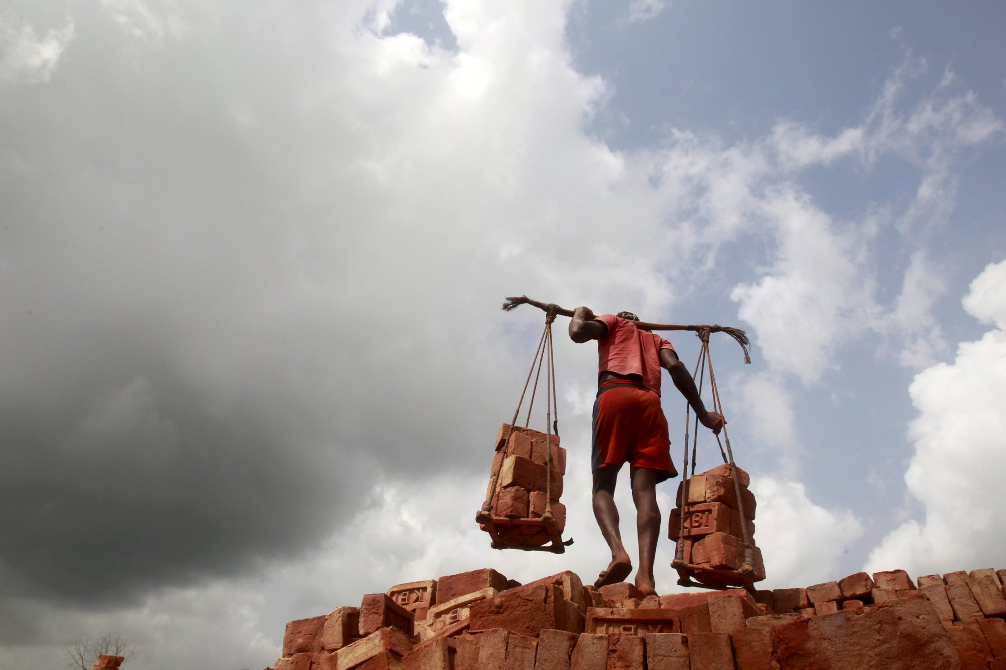 A labourer carries bricks at a brick factory on the eve of May Day or Labour Day on the outskirts of Agartala, India, April 30, 2015. (Photo by Jayanta Dey/Reuters)