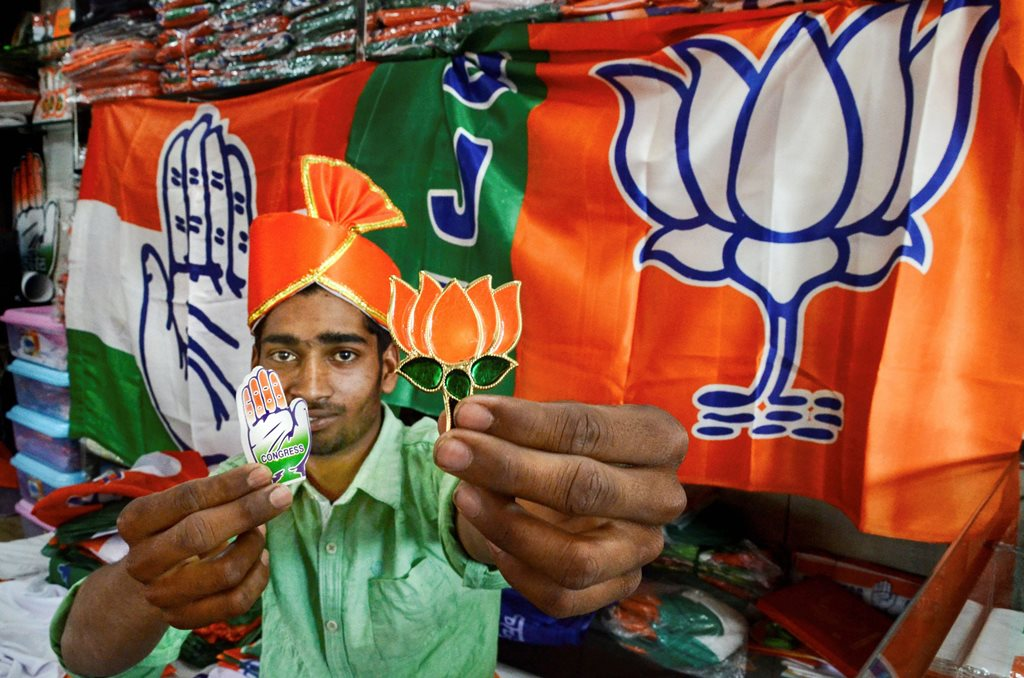 Jabalpur: A shopkeeper poses with political parties' campaign materials ahead of Lok Sabha elections 2019, in Jabalpur, Wednesday, March 13, 2019. (PTI Photo) (PTI3_13_2019_000028B)