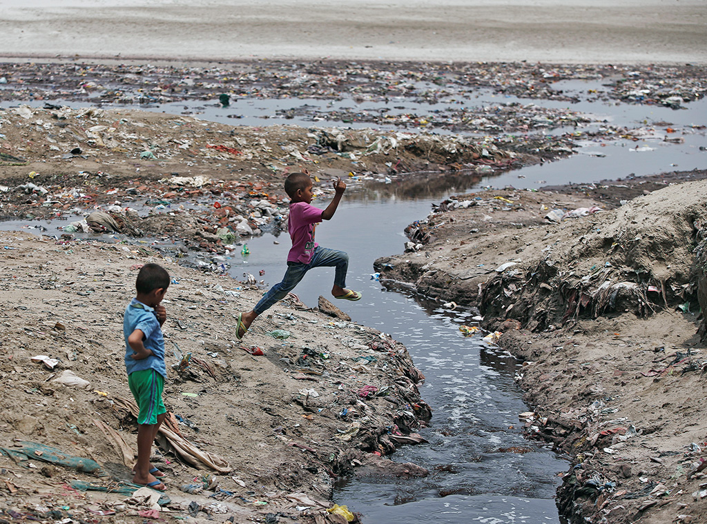 A boy jumps over a drain flowing with waste water from the leather tanneries into the river Ganges in Kanpur, India. (Photo: Reuters)