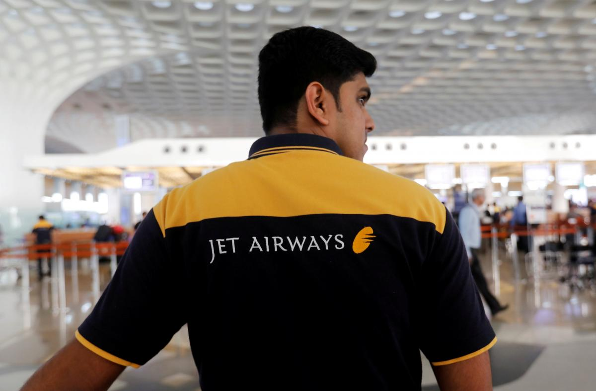 FILE PHOTO: A Jet Airways employee waits to guide passengers at a check-in counter at the Chhatrapati Shivaji International airport in Mumbai, India, February 14, 2018. REUTERS/Danish Siddiqui/File photo