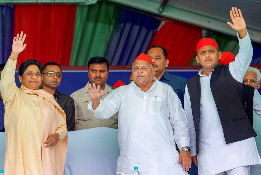 Mainpuri: Samajwadi Party patron Mulayam Singh Yadav, his son and party President Akhilesh Yadav, Bahujan Samaj Party supremo Mayawati, BSP general secretary Satish Chandra Mishra and SP's Akshay Yadav and BSP's Akash Anand wave at crowd during their joint election campaign rally in Mainpuri, Friday, April 19, 2019. Mulayam Singh Yadav and Mayawati have been bitter rivals since 1995 when SP cadres allegedly attacked the state guest house where the BSP chief had been camping with her supporters. (PTI Photo) (PTI4_19_2019_000082B)