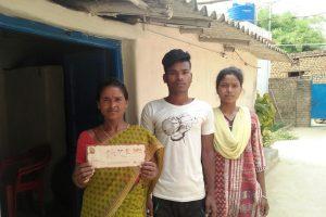 चिलिया देवी अपने बच्चों के साथ बेटी की शादी का वो कार्ड दिखाती हुईं, जिसके कवर पेज पर लिखा हुआ है कि सुगनू गांव जाने वाले दोपहिया वालों के लिए पहचान पत्र के साथ-साथ हेलमेट आवश्यक है. (फोटो: असग़र ख़ान)