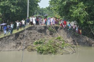 Darrang: Local people stand near an embankment which was breached by the swollen Brahmaputra river at a village, in Darrang district of Assam, Saturday, July 20, 2019. (PTI Photo)(PTI7_20_2019_000050B)