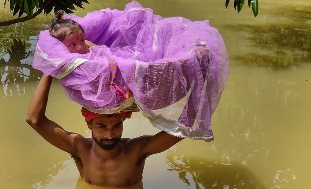 Sitamarhi: A man carries a child in a basket as he wades through a flooded street following incessant rainfall, in Sitamarhi, Friday, July 19, 2019. (PTI Photo)(PTI7_19_2019_000066B)