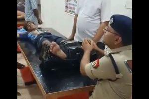 कांवड़िये का पैर दबाते शामली एसपी अजय कुमार. (फोटो: वीडियो ग्रैब)