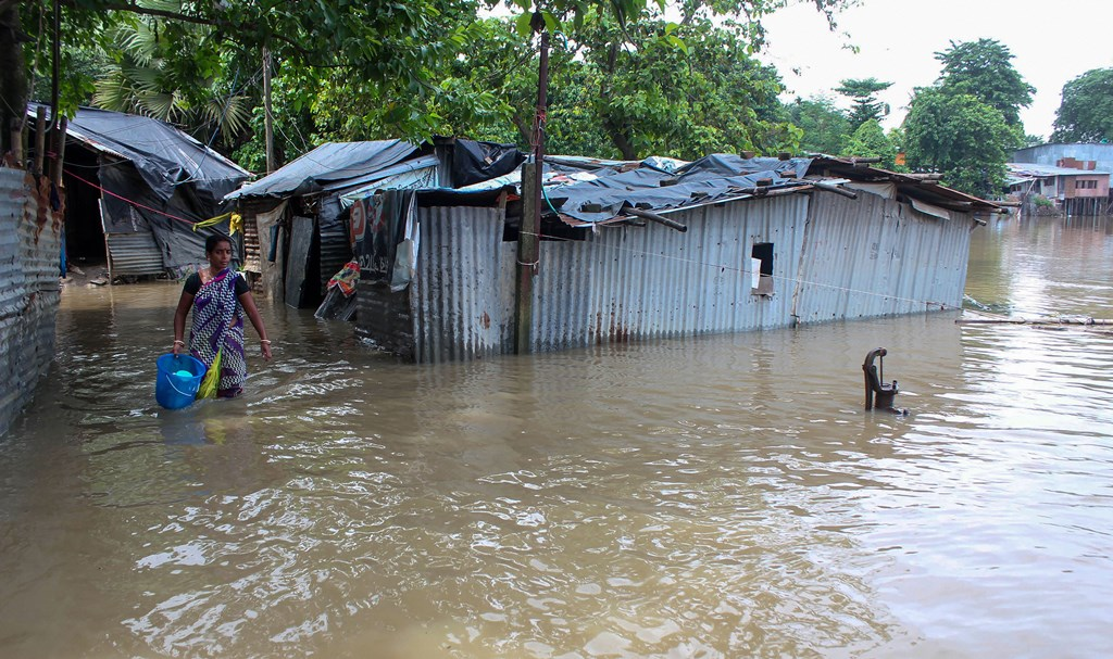 South Dinajpur: A woman wades across a flooded area after river Atreyee water level rose following incessant monsoon rainfall, at Balurghat in South Dinajpur, Thursday, July 25, 2019. (PTI Photo) (PTI7_25_2019_000122B)