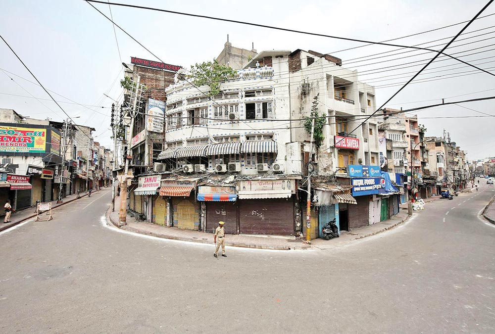 Indian policemen stand guard in a deserted street during restrictions in Jammu on August 6.Photo : Reuters