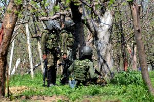 Army soldier take position behind trees during a gun battle between security forces and militants in Shopian, of South Kashmir on Sunday. Photo: PTI/S. Irfan/File