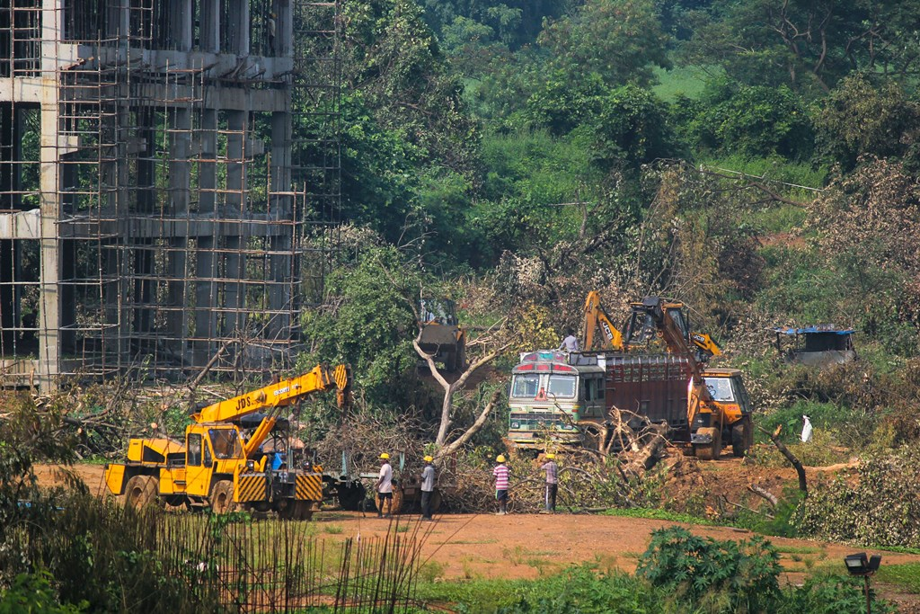Mumbai: A crane lifts the the fallen trees to be carried away for building a construction site of metro car parking shed at Aarey Colony, Mumbai, Monday, Oct. 7, 2019. The Supreme Court on Monday restrained authorities from cutting any more trees in Mumbai's Aarey colony the shed before further hearing on Oct. 21. (PTI Photo) (PTI10_7_2019_000202B)