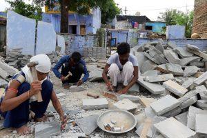 बूंदी ज़िले के बुधपुरा में अपने घर के आगे पड़े पत्थरों से कॉबल बनाते श्याम, उनकी बहन मीना और 16 साल का चचेरा भाई राजू. (सभी फोटो: माधव शर्मा)