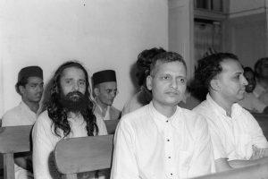 महात्मा गांधी की हत्या के मामले में दिल्ली में हुई सुनवाई के दौरान नाथूराम गोडसे (पहली पंक्ति में बाएं) और सावरकर (सबसे पीछे दाएं) (फोटो साभार: फोटो डिवीज़न/भारत सरकार)