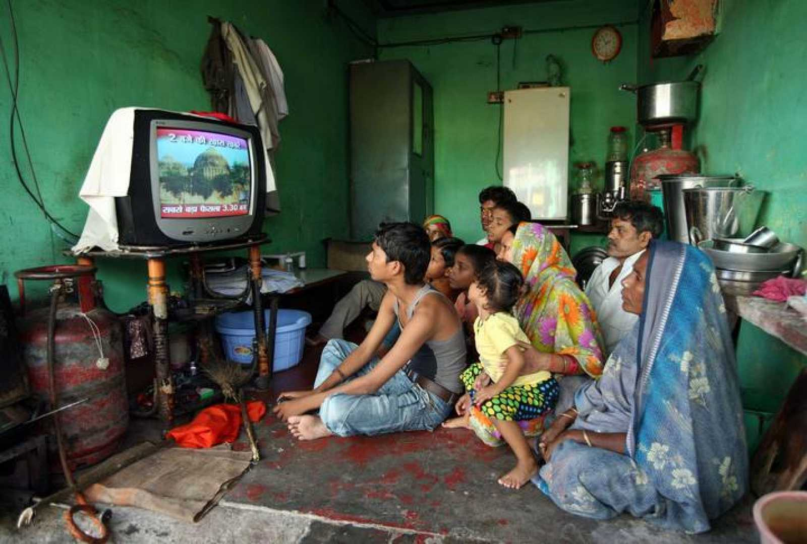 A family watches a TV news channel in a room in Ayodhya September 30, 2010. REUTERS/Mukesh Gupta